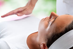 Woman at reiki session with therapist hand in background. Close up portrait of young woman relaxing at reiki session with therapist hand in background royalty free stock images
