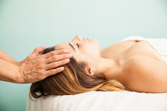 Woman in a reiki therapy session. Profile view of a cute young women getting her energy balanced at a reiki session in a health clinic and spa stock photography