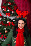 Woman with reindeer ears and Xmas tree Royalty Free Stock Photography