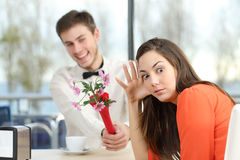 Woman rejecting a geek boy in a blind date. Disgusted women rejecting a geek boy offering flowers in a blind date in a coffee shop interior stock photo