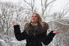 A woman rejoices in the falling snow. Walking in the park in the snow. Happy girl in winter park. A woman rejoices in the falling snow. Walking in the park in Stock Photos