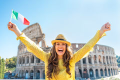 Woman rejoicing with italian flag in rome. Portrait of happy young woman rejoicing with italian flag in front of colosseum in rome, italy stock images