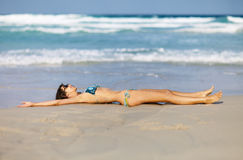 Woman relax on the beach wrapped in towel Stock Images