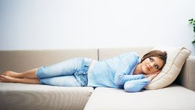 Woman relax at home. Young beautiful woman lying on sofa Royalty Free Stock Images