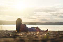 Woman relax and lay down in the sunset on the beach. Royalty Free Stock Photo