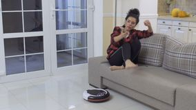 Woman relax with phone at sofa while vacuum-cleaning robot cleans the floor. Young woman sits at the sofa at home and relaxes with her phone. She`s stretching stock video footage