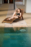 Woman relax by the pool side Stock Image