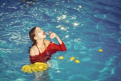 Woman relax in spa pool. woman with tropical fruit in pool. Vitamin in banana at girl sitting near water. Dieting and royalty free stock photos