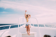 Woman relax in sunglasses on white yacht in on ocean waves Stock Image