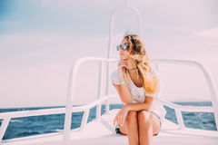 Woman relax in sunglasses on white yacht in on ocean waves Stock Photo