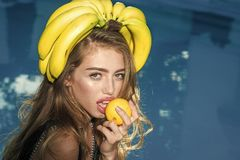 Woman relax in swimming pool with lemon. Dieting and healthy organic food, vegetarian. Sexy woman with tropical fruit in. Pool. Vitamin in banana at girl near Royalty Free Stock Photo