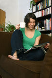 Woman relaxe in living room. Smiling woman with cup of coffee reading a magazine in the sofa royalty free stock image