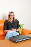 Woman relaxed on couch with laptop computer Stock Photography