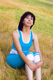 Woman relaxed outdoors. Relaxed woman seated in the grass outdoors Royalty Free Stock Photos