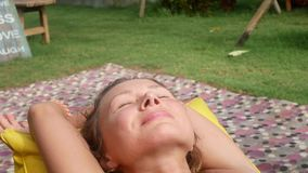 Woman relaxes in a bag-chair on a clearing with green grass stock video