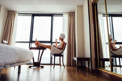 Woman relaxes with cup of tea near the panorama window in luxury Royalty Free Stock Image