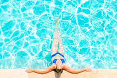 Woman relaxes at the edge of pool Royalty Free Stock Images