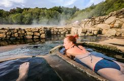 Woman relaxes and enjoys natural hot thermal water roman spa. Outdoor pools and baths with hot, smoking thermal water and hot spring of Aquis Querquennis royalty free stock photo