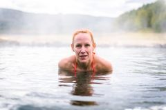 Woman relaxes and enjoys natural hot thermal water roman spa. Outdoor pools and baths with hot, smoking thermal water and hot spring of Aquis Querquennis stock photos