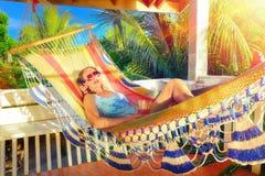 Woman relaxes on a hammock in a tropical garden Stock Photos