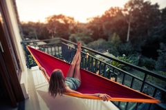Woman relaxes in the hammock. Set on a balcony and enjoys sunset and tropical garden view. Tilt shift effect applied stock image