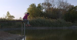 Woman relaxes by the lake sitting on the edge of a wooden jetty , swing legs on the sunset. Woman relaxes by the lake sitting on the edge of a wooden jetty stock video footage