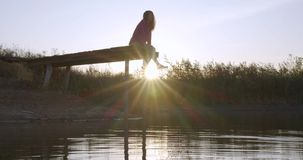 Woman relaxes by the lake sitting on the edge of a wooden jetty , swing legs on the sunset. Woman relaxes by the lake sitting on the edge of a wooden jetty stock video