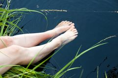 Woman relaxes by the lake sitting on the edge of a wooden jetty , swing one`s feet near the water surface. Sunny joyful summer day or evening concept stock photography