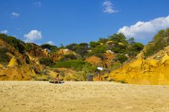 A woman relaxes and sunbaths on a sunny beach in Portugal royalty free stock photos
