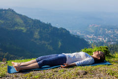 Woman relaxes in yoga asana Savasana outdoors. Woman relaxes in yoga asana Savasana - corpse pose outdoors in Himalayas. Himachal Pradesh, India royalty free stock images