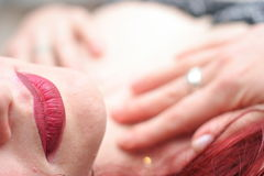 Woman relaxing. Closeup of red haired woman relaxing with focus on lips in foreground Stock Photo