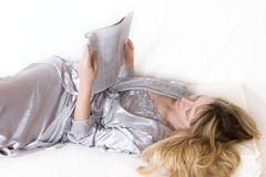 A woman relaxing (2). A woman in a silver silk robe holding a magazine and reading Royalty Free Stock Photos