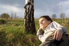 Woman is relaxing. Woman with pensive look lie at field near birch tree Royalty Free Stock Photo