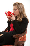 Woman relaxing. Attractive blond woman sitting down and drinking a cup of coffee while still in work clothes Royalty Free Stock Photography