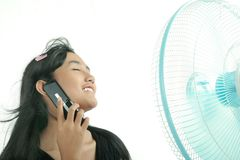 Woman relaxing. With electric fan while calling Stock Images