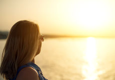 Woman relaxing against sunset. Royalty Free Stock Photography