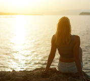 Woman relaxing against sunset. Stock Images