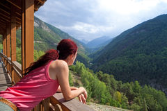 Woman Relaxing In The Alps. Woman tourist leaning over a patio railing admiring the beautiful valley scenery in the Alps Royalty Free Stock Photography