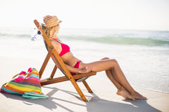 Woman relaxing on an armchair on the beach Royalty Free Stock Photos