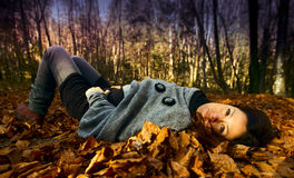 Woman relaxing in autumn. Beautiful woman lying on autumn leaves in the woods. Vivid fall colored foliage in a woodsy forest in autumn Stock Photography