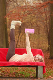 Woman relaxing in autumn fall park reading book. Royalty Free Stock Images
