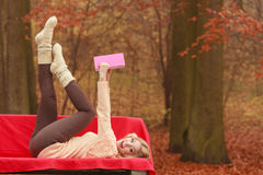 Woman relaxing in autumn fall park reading book. Royalty Free Stock Photos