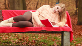 Woman relaxing in autumn fall park reading book. Stock Photos