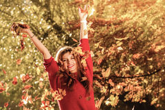Woman relaxing in autumn park throwing leaves up in the air Stock Images