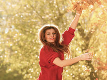 Woman relaxing in autumn park throwing leaves up in the air Royalty Free Stock Photo