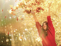 Woman relaxing in autumn park throwing leaves up in the air Stock Photos