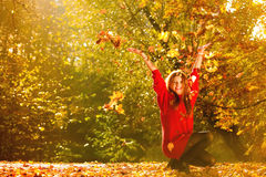 Woman relaxing in autumn park throwing leaves up in the air Royalty Free Stock Photos