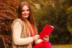 Woman relaxing in autumnal park reading book Royalty Free Stock Photography