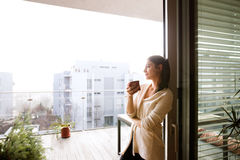 Woman relaxing on balcony holding cup of coffee or tea Royalty Free Stock Images