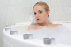Woman relaxing in bath with candles Stock Photography